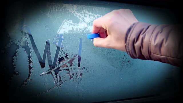winter written on a frosty glass - brina ghiaccio video stock e b–roll