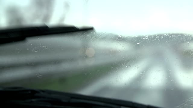 Wipers removing rain in slow motion close up video