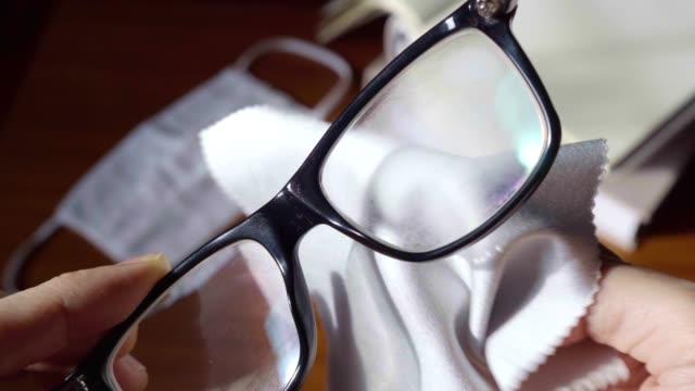 wischen neblige gläser mit mikrofasertuch - brille stock-videos und b-roll-filmmaterial