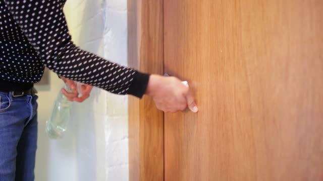 wiping the door handle - igiene video stock e b–roll