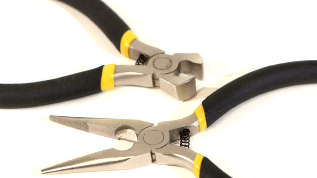 Wire cutters and mini cutters on white, rotation, close up