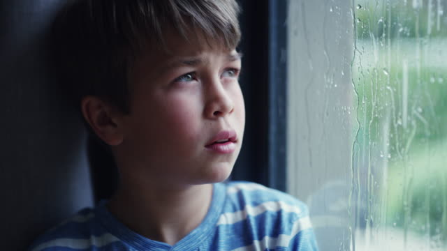 I wish the rain had an off switch 4k video footage of a sad young boy watching the rain through a window at home one boy only stock videos & royalty-free footage