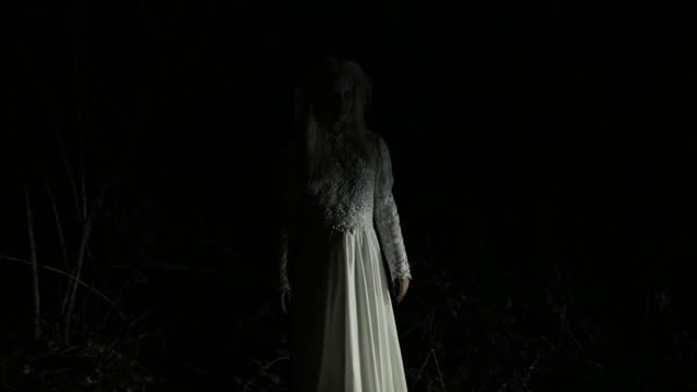Witch in white dress appearing on the road Bizarre lady dressed in white wedding dress looking at camera from the dark ghost stock videos & royalty-free footage