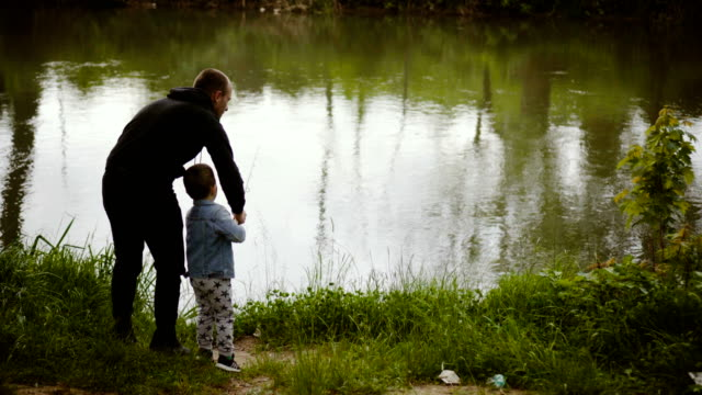 With father on fishing Father is teaching his little son to fish. fishing rod stock videos & royalty-free footage
