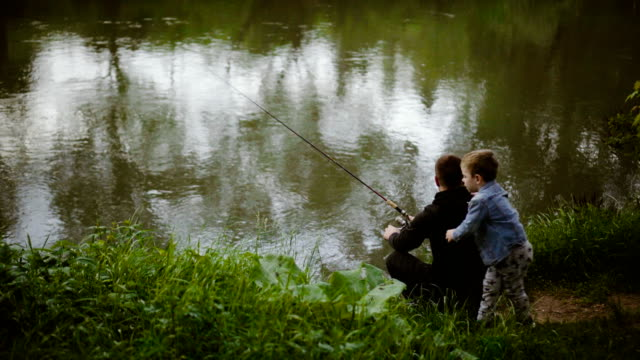 With father on fishing Father and son are fishing on the river. fishing rod stock videos & royalty-free footage