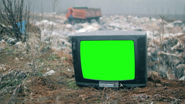 TV with green screen at the landfill site while snowing