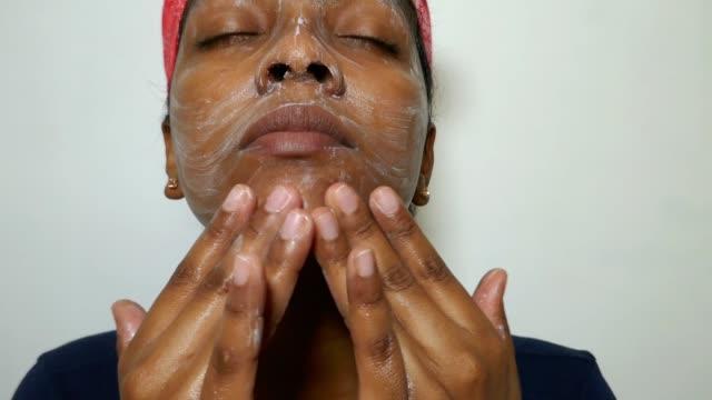 senza trucco, la donna sui 20 anni si lava il viso con le dita. routine mattutina, toelettatura, cura della persona, concetto di trattamento della bellezza della cura della pelle dei cosmetici naturali - afro americano video stock e b–roll