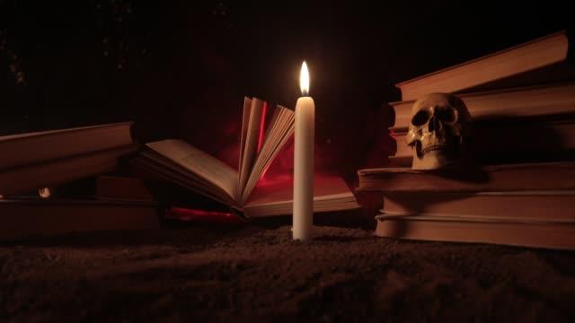 guidens skrivbord. ett skrivbord upplyst av levande ljus. en mänsklig skalle, gamla böcker på sand yta. halloween stilleben bakgrund med en olika element på mörk tonad dimmig bakgrund. reglaget som sköt - halloween background bildbanksvideor och videomaterial från bakom kulisserna