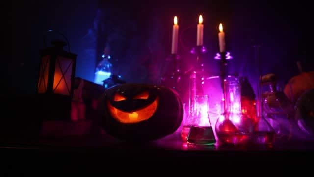 guidens skrivbord. skräck halloween koncept. magiska brygder i flaskor på träbord med böcker och ljus. halloween stilleben bakgrund med olika element på mörkt tonas dimmigt bakgrund. - halloween background bildbanksvideor och videomaterial från bakom kulisserna