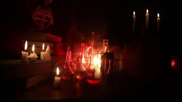 vidéos et rushes de bureau du magicien. concept d'halloween d'horreur. potions magiques dans des bouteilles sur la table en bois avec des livres et des bougies. fond de nature morte d'halloween avec différents éléments sur le fond brumeux tonique foncé. - charmeur