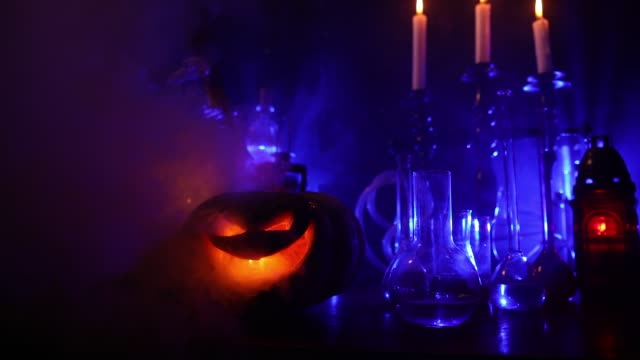 wizard's desk. horror halloween concept. magic potions in bottles on wooden table with books and candles. halloween still-life background with different elements on dark toned foggy background. - halloween background filmów i materiałów b-roll