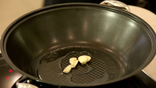 Wok with hot oil and crushed garlic video