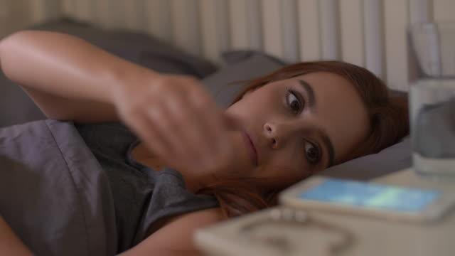 vaknat med ett telefonmeddelande. ung kvinna sover. - telefonmeddelande bildbanksvideor och videomaterial från bakom kulisserna