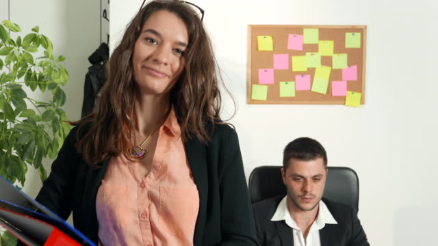 Womam looking at camera in office space video