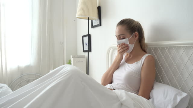 woman a cough and sick with mask on bed at home - face mask stock videos & royalty-free footage