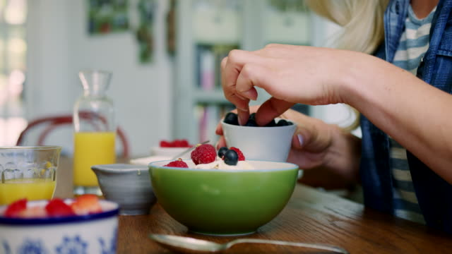 vídeos de stock e filmes b-roll de woman adding blueberries and honey to granola - granola