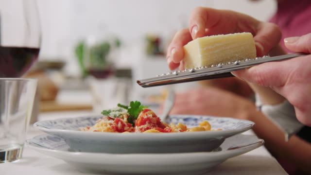 Woman adding cheese with a grate to pasta Close-up of a woman adding cheese with a grater to the pasta while sitting at dining table. Female garnishing pasta with cheese at cooking class. garnish stock videos & royalty-free footage