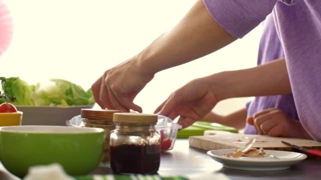 vídeos de stock, filmes e b-roll de mulher que adiciona legumes frescos à caixa de almoço da escola da sua filha - almoço