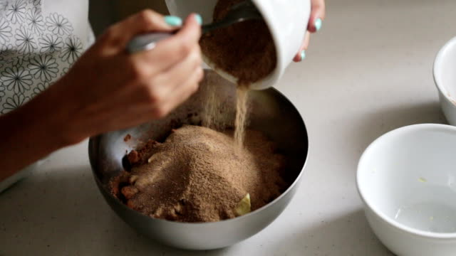 Woman adding ingredients to a bowl for cooking home made chocolate video