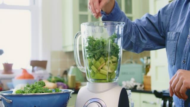 frau, die zugabe von kale und wasser in den mixer in der küche - grünkohl stock-videos und b-roll-filmmaterial