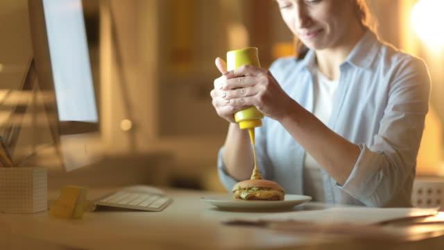 vídeos de stock, filmes e b-roll de mulher, adicionando a mostarda no hambúrguer - junk food