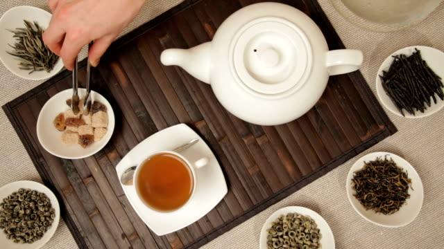 stockvideo's en b-roll-footage met woman adds brown sugar in cup of tea - camelia white