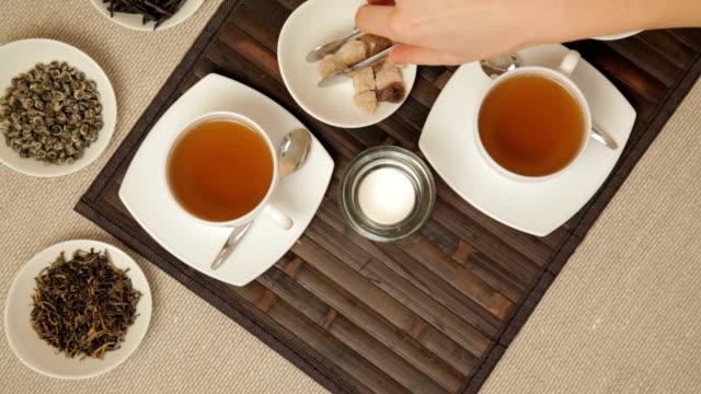 stockvideo's en b-roll-footage met woman adds brown sugar in cups of tea - camelia white