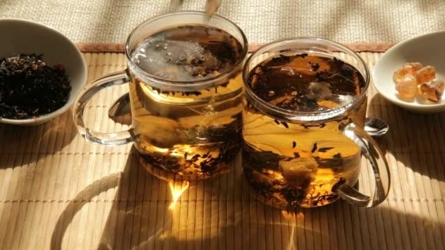 Woman adds brown sugar in glass of tea video