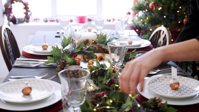 A woman adjusting festive decorations on a Christmas dinner table, detail shot of hands, elevated view