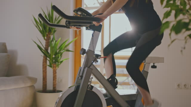 SLO MO Woman adjusting the exercise bike Slow motion dolly shot of an unrecognizable woman adjusting the strength while cycling on the exercise bike at home. Conceptual shot of the self isolation time. Shoot in 8K resolution. exercise bike stock videos & royalty-free footage
