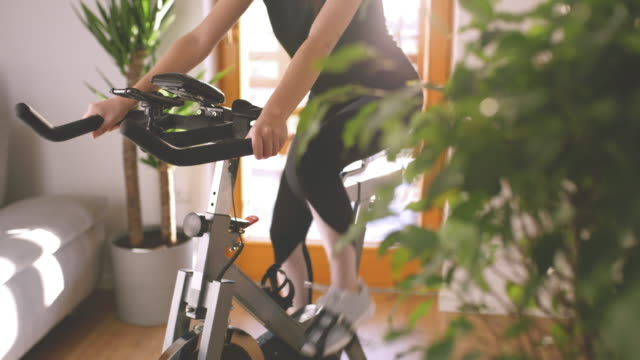 SLO MO Woman adjusting the exercise bike while cycling on it Slow motion dolly shot of a young woman adjusting the strength while cycling on the exercise bike at home. Conceptual shot of the self isolation time. Shoot in 8K resolution. exercise bike stock videos & royalty-free footage