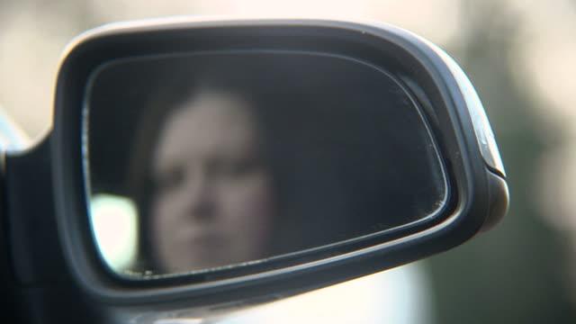 woman adjusts wing mirror - ayarlamak stok videoları ve detay görüntü çekimi
