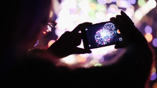A woman admires the fireworks in the night sky. Take pictures with your smartphone. 4k 10 bit video A woman admires the fireworks in the night sky. Take pictures with your smartphone pyrotechnic effects stock videos & royalty-free footage