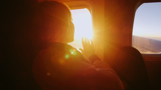 a woman admires the sunrise from the window of the plane. touches her hand to the orange rays - sedili aereo video stock e b–roll