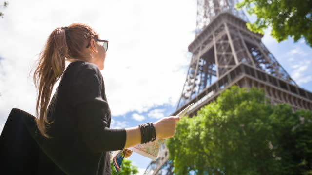 woman admiring eiffel tower while walking the streets of paris on a sunny day - french architecture stock videos & royalty-free footage