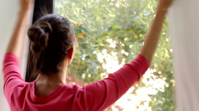 женщина против окна закрытия шторы - близко к стоковые видео и кадры b-roll