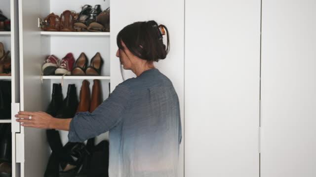 vídeos de stock e filmes b-roll de woman alone arranging many shoes in large wardrobe - arranjo