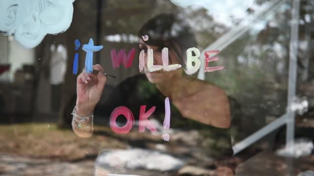 vídeos y material grabado en eventos de stock de mujer sola casa dibujo covid-19 arco iris símbolo en la ventana del pasillo - stay home