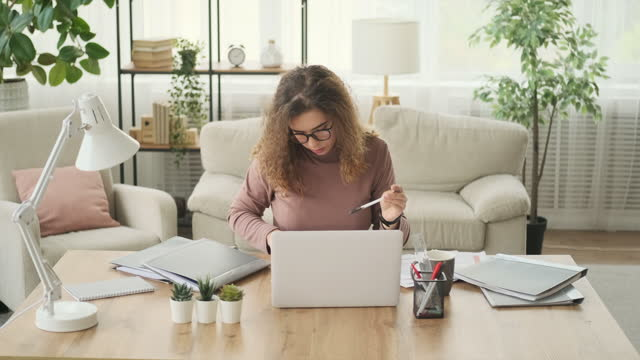 Woman analyzing documents and working on laptop