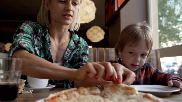 Woman and 5 year boy eating pizza in cafe