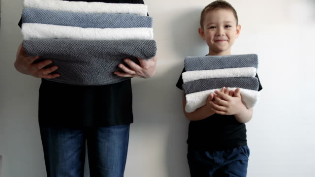女性は、壁の近くに立って、別のタオルのスタックを保持している少年。家族の概念。 - 楽しい 洗濯点の映像素材/bロール