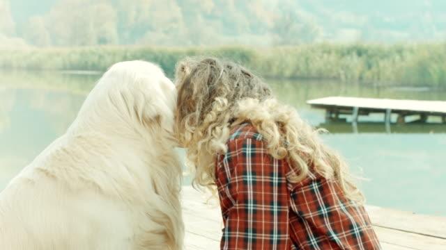 vidéos et rushes de femme et un chien au lac - femme seule s'enlacer