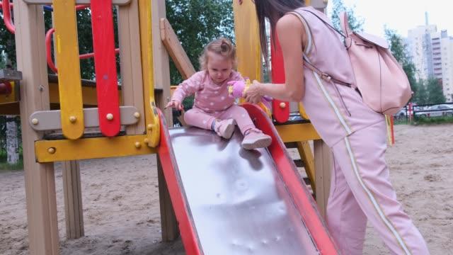 vídeos y material grabado en eventos de stock de mujer y una niña se deslizan hacia abajo en un tobogán de los niños en el patio de recreo. tiempo de la madre - deslizar
