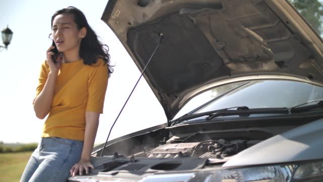 kvinna och trasiga bil och ringer för hjälp på telefon - bilolycka bildbanksvideor och videomaterial från bakom kulisserna