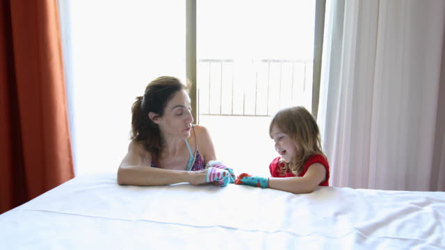 woman and child making theater with socks in their hands video