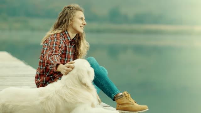 vidéos et rushes de femme et chien assis sur la jetée et à la recherche à distance - femme seule s'enlacer