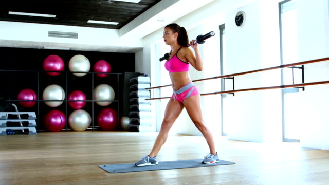 Woman and doing lunge with barbell and flexing muscles in gym video
