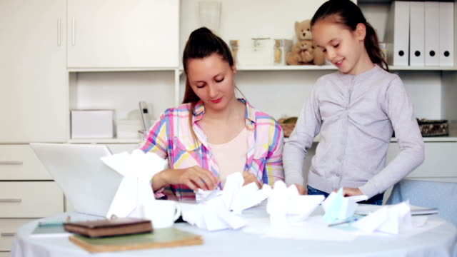 woman and girl making airplanes of paper