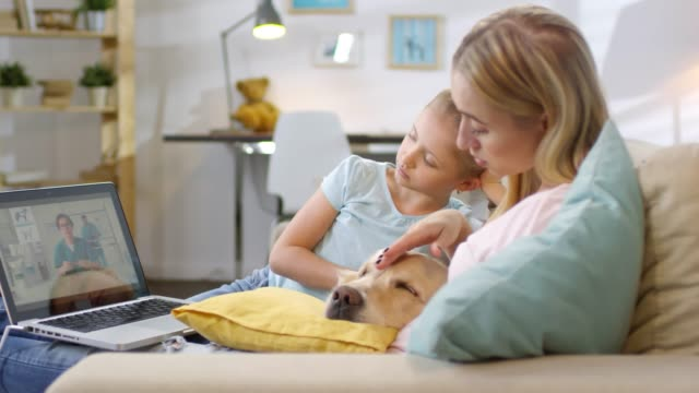 Woman And Girl Petting Dog And Consulting With Online Vet