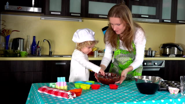 woman and her cute little daughter filling muffin cases video